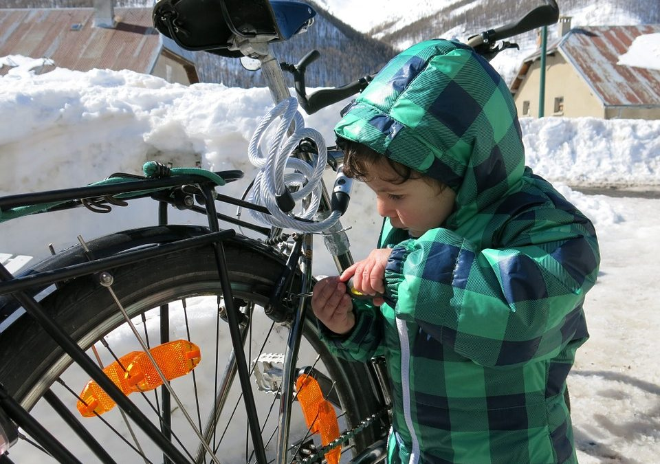 child using tools to repair a bicycle