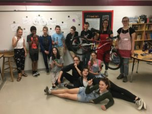 Classroom of kids, posing and being silly, holding bike tools.
