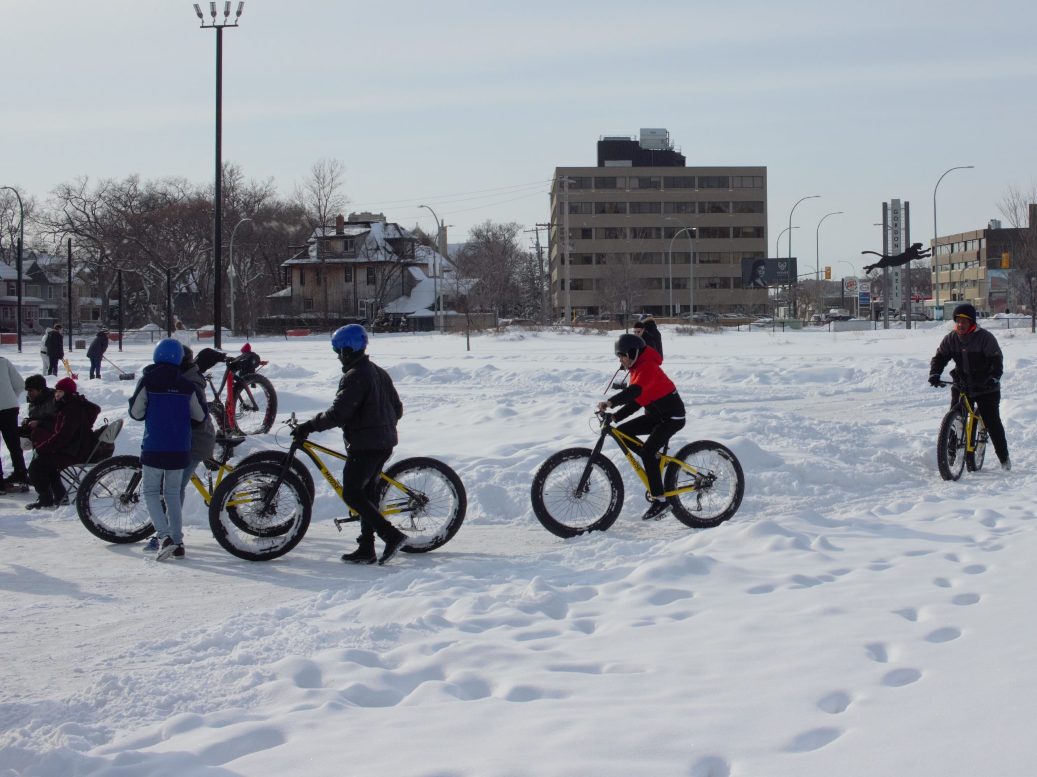 Students riding bicycles through paths cleared in snow on a schoolyard
