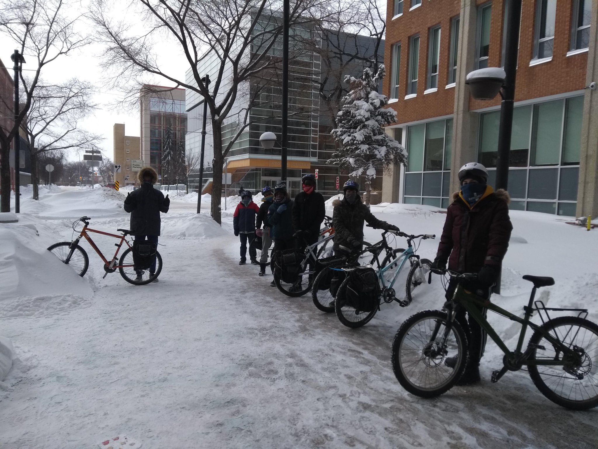 Small group of students and a teacher bundled up, standing with their bicycles