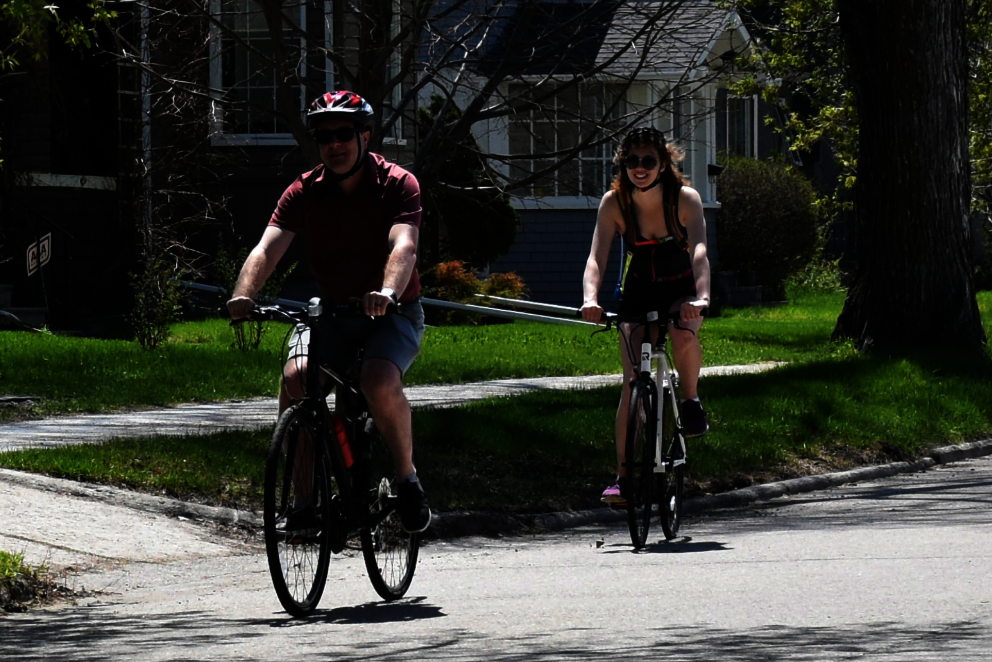 Man and woman riding single file down a calm residential street.